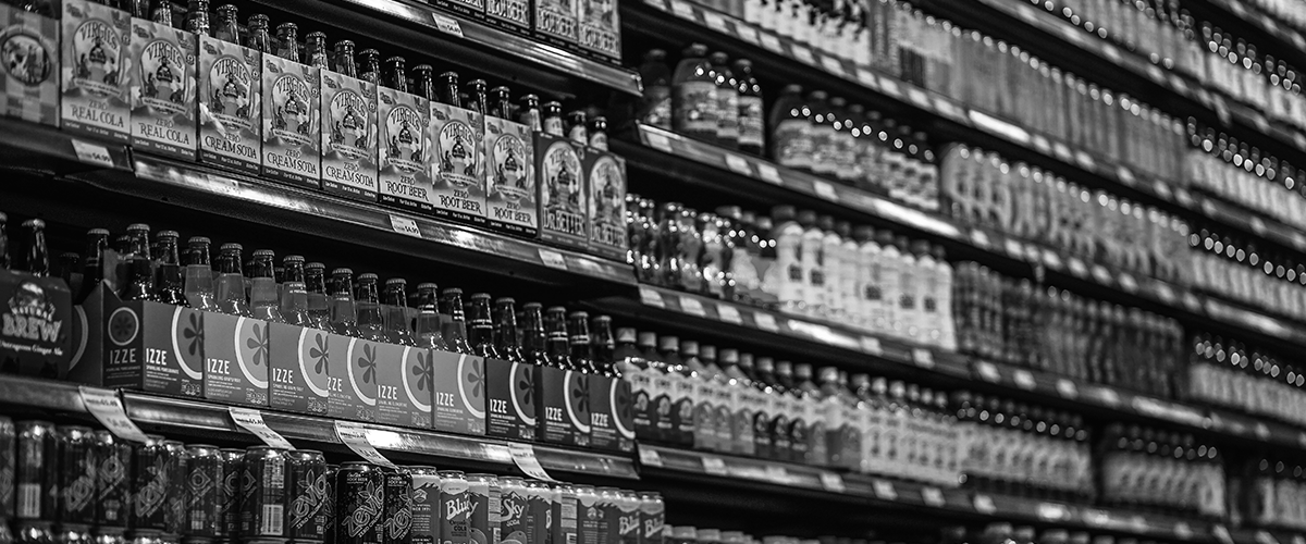 category managers bottles on a shelf at supermarket