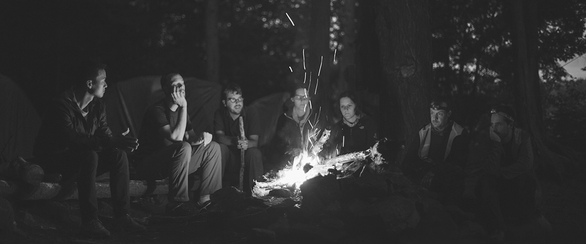 people sitting around a campfire telling stories